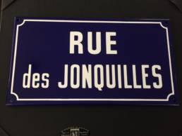Plaque émaillée traditionnelle de rue avec fond bleu et un filet blanc
