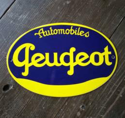 Plaque émaillée ovale avec un ancien logo de Peugeot en deux couleurs