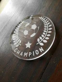 Petite médaille sportive réalisé en plexiglas transparent pour un collier
