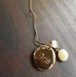 Médaillon doré avec une gravure mécanique au diamant pour marquer le prénom.