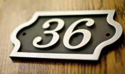 Numéro de rue en inox découpé en forme de plaque à oreilles