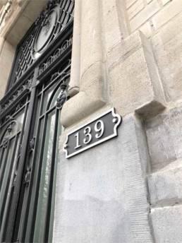 Numéro de rue en inox découpé sur un bâtiment Haussmannien