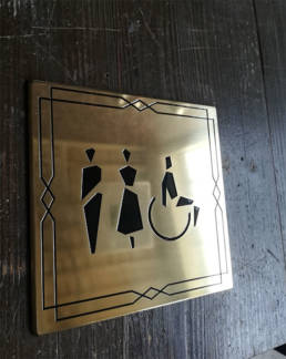 Signalétique intérieure en laiton vernis pour indiquer les toilettes